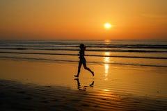 Siluetta di funzionamento del pareggiatore della donna sulla spiaggia di tramonto con la riflessione, la forma fisica e lo sport fotografia stock libera da diritti