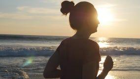 Siluetta di funzionamento della giovane donna sulla spiaggia del mare al tramonto Ragazza che pareggia lungo la riva dell'oceano  Immagine Stock