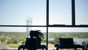 Siluetta di funzionamento della ragazza sulla pedana mobile e di esaminare la grande finestra Colpo da sinistra a destra del carr video d archivio