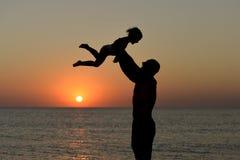 Siluetta di gioco papà e della figlia sui precedenti del tramonto del mare fotografie stock