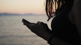 Siluetta di giovane castana facendo uso del suo Smartphone mentre stando sul lungonmare al tramonto video d archivio