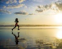 Siluetta di giovane donna asiatica del corridore di sport nell'allenamento corrente Fotografie Stock