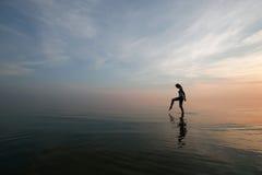 Siluetta di giovane donna che guada nel mare Fotografie Stock