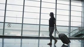 Siluetta di giovane donna graziosa di affari che cammina all'aeroporto con i suoi bagagli mentre aspettando la sua coda la regist video d archivio