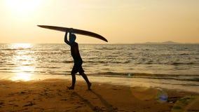 Siluetta di giovane funzionamento felice dell'uomo della spuma con i bordi di spuma lunghi al tramonto sulla spiaggia tropicale s video d archivio