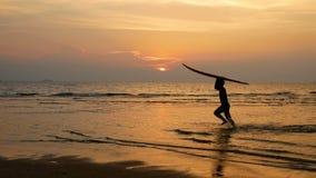 Siluetta di giovane funzionamento felice dell'uomo della spuma con i bordi di spuma lunghi al tramonto sulla spiaggia tropicale s archivi video