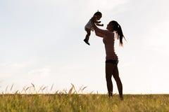 Siluetta di giovane madre che tiene felicemente il suo bambino su nell'aria su un campo erboso fotografia stock libera da diritti