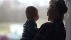 Siluetta di giovane madre con il suo bambino Una giovane donna tiene con attenzione il suo bambino e guarda fuori la finestra att stock footage