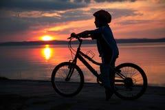 Siluetta di giovane ragazzo, al tramonto, bicicletta di guida Fotografia Stock Libera da Diritti