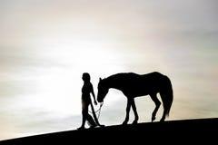 Siluetta di giovane Rider And Her Horse femminile Fotografia Stock Libera da Diritti