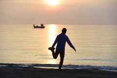 Siluetta di giovane uomo di sport che allunga gamba dopo l'allenamento corrente all'aperto sulla spiaggia al tramonto immagine stock