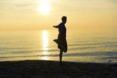Siluetta di giovane uomo di sport che allunga gamba dopo l'allenamento corrente all'aperto sulla spiaggia al tramonto fotografie stock libere da diritti