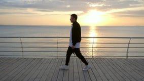 Siluetta di giovane uomo moderno d'avanguardia che cammina lungo l'argine di legno vicino al mare o all'oceano Uomo nel bombardie video d archivio