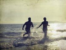 Siluetta di giovani anni dell'adolescenza felici che giocano sulla spiaggia Fotografia Stock