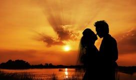 Siluetta di giovani sposa e sposo sul tramonto immagine stock libera da diritti