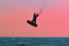 Siluetta di kitesurfer sul fondo di tramonto Immagini Stock
