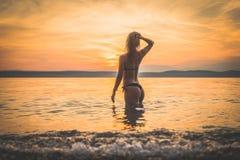 Siluetta di modello della giovane ragazza attraente nell'acqua fotografia stock libera da diritti