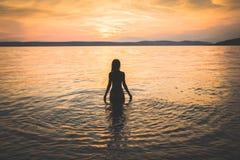 Siluetta di modello della giovane ragazza attraente nell'acqua fotografia stock