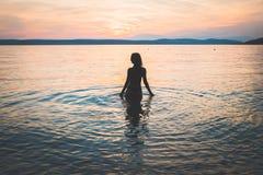 Siluetta di modello della giovane ragazza attraente nell'acqua immagini stock