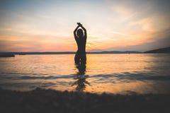 Siluetta di modello della giovane ragazza attraente nell'acqua fotografie stock libere da diritti