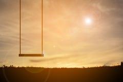 Siluetta di oscillazione al tramonto del cielo Immagine Stock