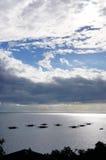 Siluetta di parecchie piccole barche che vanno alla deriva nell'oceano Fotografia Stock