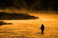 Siluetta di pesca di pesca con la mosca dell'uomo alla luce solare dorata del fiume Immagini Stock