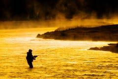 Siluetta di pesca di pesca con la mosca dell'uomo alla luce solare dorata del fiume Fotografie Stock