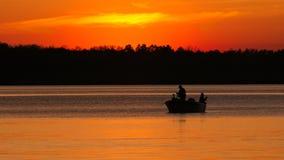 Siluetta di pesca del figlio e del padre sul lago al tramonto immagini stock