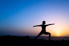 Siluetta di posa di yoga di addestramento della donna Fotografia Stock