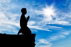 Siluetta di pregare dell'uomo Immagini Stock