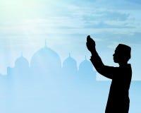 Siluetta di pregare musulmano della gente Immagini Stock Libere da Diritti