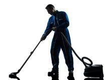 Siluetta di pulizia dell'aspirapolvere del portiere dell'uomo Fotografia Stock