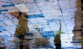 Siluetta di riflessione di una giovane donna sotto l'ombrello rosso sui rai Immagine Stock