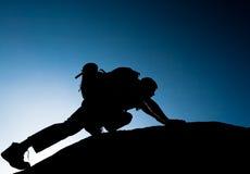 Siluetta di scalata dell'adulto giovane alla cima della sommità Immagine Stock Libera da Diritti