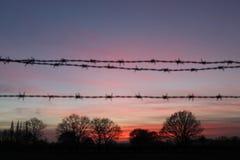 Siluetta di tramonto del filo spinato Fotografie Stock