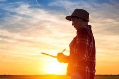 Siluetta di tramonto delle note femminili di scrittura dell'agricoltore nel campo Immagini Stock