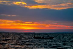 Siluetta di tramonto di una barca sul lago Immagine Stock Libera da Diritti