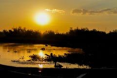 Siluetta di tramonto di una barca sul lago Fotografie Stock