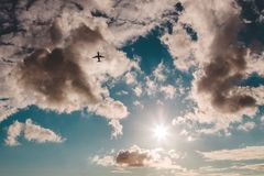 Siluetta di un aereo di partenza contro un cielo parzialmente nuvoloso con splendere del sole fotografia stock