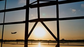 Siluetta di un aeroplano che decolla al tramonto all'aeroporto di Pechino nei precedenti di una finestra fotografie stock libere da diritti