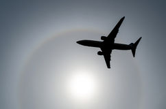 Siluetta di un aeroplano nel sole del cielo e dell'alone nelle nuvole Fotografia Stock