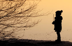 Siluetta di un bambino che gioca in natura al tramonto Fotografie Stock Libere da Diritti