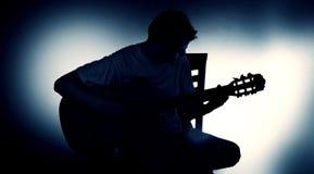 Siluetta di un chitarrista con una chitarra acustica che si siede su una sedia, fondo nero fotografia stock