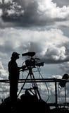 Siluetta di un cineoperatore della TV contro il cielo nuvoloso Immagine Stock