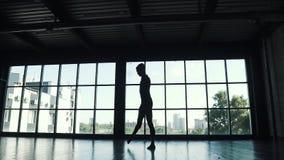 Siluetta di un dancing maschio del ballerino di balletto contro lo sfondo di grande finestra il ballerino balla elegante in archivi video