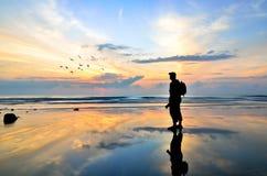 Siluetta di un fotografo che guarda alla volata degli uccelli Fotografia Stock