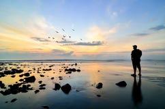 Siluetta di un fotografo che guarda alla volata degli uccelli Immagini Stock