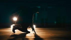 Siluetta di un freerunner del giovane che fa i trucchi acrobatici su parcheggio sotterraneo, movimento lento archivi video