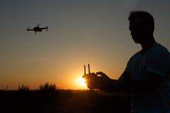 Siluetta di un fuco di pilotaggio dell'uomo nell'aria con un regolatore a distanza in sue mani sul tramonto Il pilota prende le f Immagine Stock
